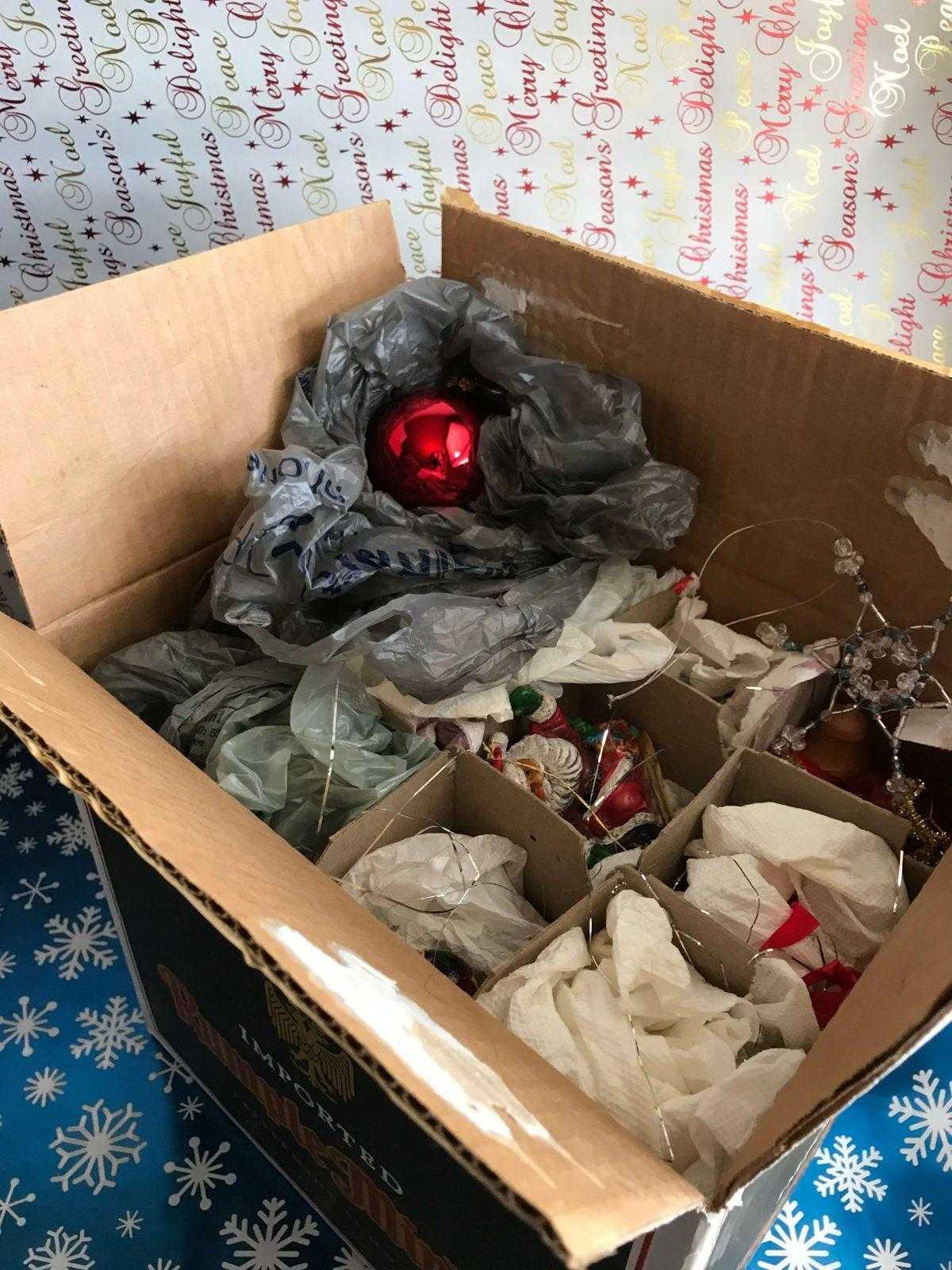 Weihnachtsdekoration einpacken in einen Flaschenkarton